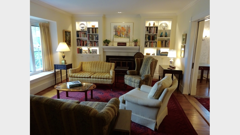 Furnished livingroom with built-in book cases and a view across the hills to Mount Ascutney.