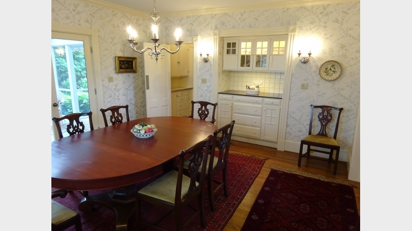 The spacious dining room, with a built-in sideboard, opens to the living room on one side, and the porch on the other.