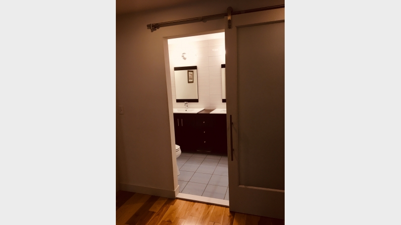 Main level bathroom with barn door entry and oversized tile shower with rain shower head
