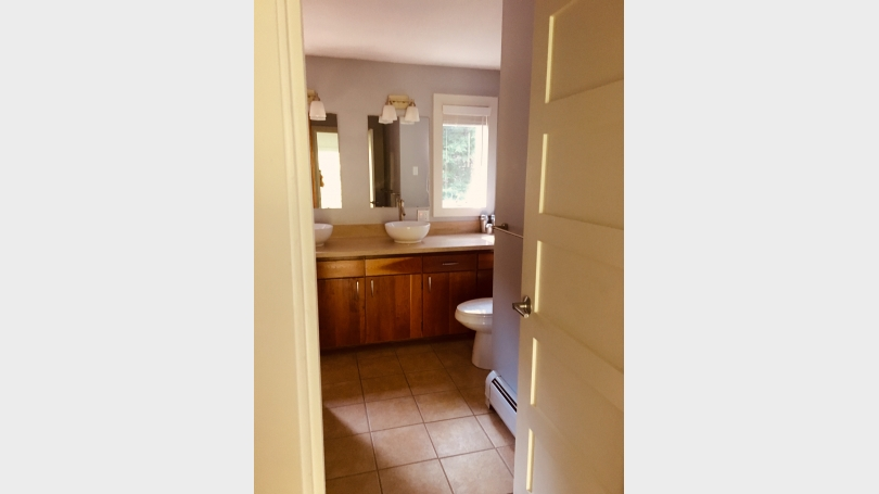 Upper level bath with shower/bathtub and two sinks.  Cherry cabinetry.