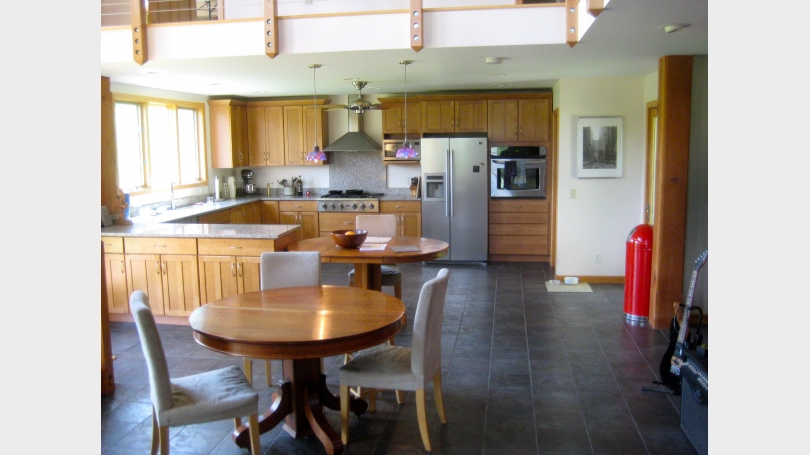 Large kitchen with granite countertops, stainless steel appliances and lots of storage space.