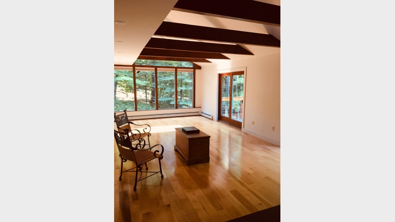 Open living room with beams and soaring windows with access to the deck