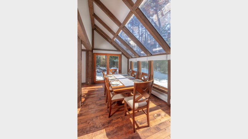 Dining area includes cathedral ceiling, skylights and a wall of windows.