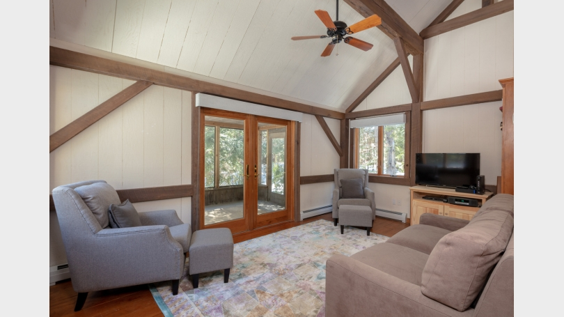 Den with sleep sofa leads to screened in porch.