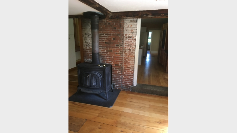 wood stove in entrance to supplement gas heat