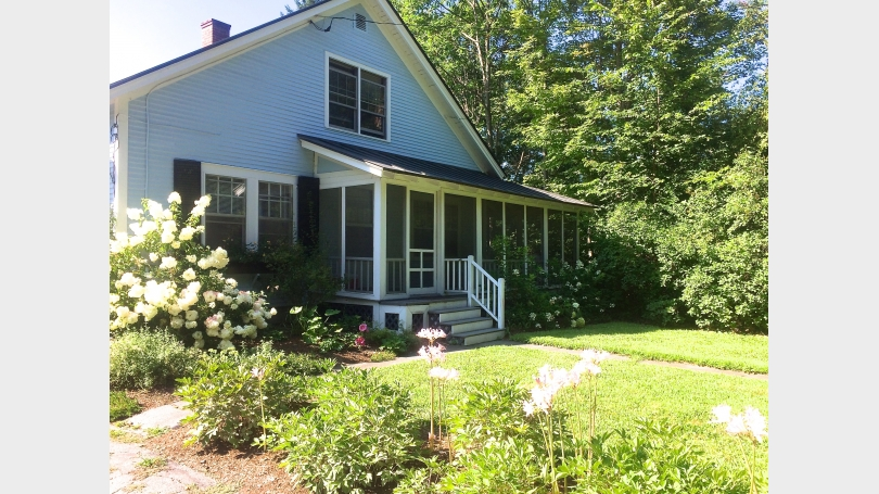 Cottage front with wrap-around screened porch